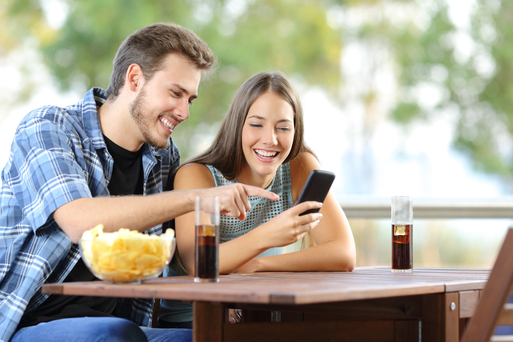 Couple sharing a smart phone sitting on a hotel or home terrace