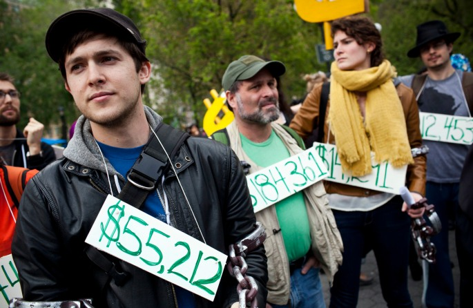 Occupy Wall Street demonstrators participating in a street-theater production wear signs around their neck representing their student debt during a protest against the rising national student debt in Union Square, in New York, April 25, 2012.